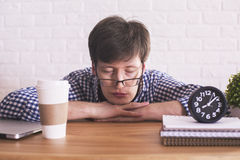 Young man sleeping in office. Young caucasian male sleeping on wooden office desktop with coffee cup, clock and notepads on white brick background Royalty Free Stock Photo
