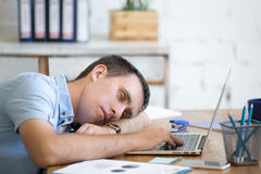 Young man sleeping on office desk Stock Photo