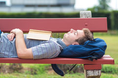 Young man sleeping in the park with a book. Young man sleeping in the park on the bench with a book Royalty Free Stock Images
