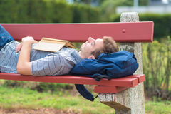 Young man sleeping in the park with a book. Young man sleeping in the park on the bench with a book Stock Photos