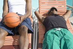 Young Man Sleeping On Sunlounger. Young African American men sleeping on sunlounger with friend sitting besides Royalty Free Stock Photography