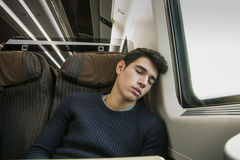 Young man sleeping while traveling on a train Stock Images