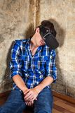 Young Man in VR Glasses. Young Man sleeping in Virtual Reality Glasses by the Old Wall in the Derelict House Royalty Free Stock Image