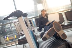 Young man sleeping while waiting in airport terminal. Young asian man sleeping while waiting for connecting flight on bench in the international airport terminal Royalty Free Stock Photography