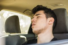 Young man sleeping at the wheel driving his car Stock Photo