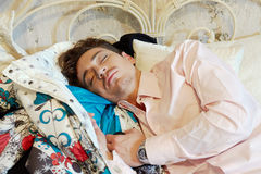 Young man sleeps on bed Stock Photography