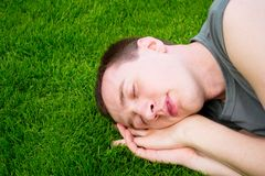 The young man sleeps on  green grass Stock Photos