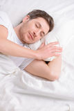 Young man sleeps in his bed. Snooze minutes. Attractive young single man doses off in his bed in the morning Stock Images