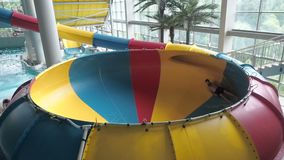 A young man slides down from a water slide in a water park water park people ride from the slides and jump into the pool.  stock footage