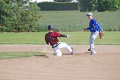A young man sliding into second base. A high school baseball player sliding in to second base, in a game played in the greater Willamette Valley of Oregon. On a Stock Images
