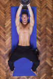 Young man slim fit chest dumbbell pullover elevated view.  Royalty Free Stock Image