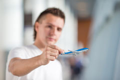 Young man with small airplane in airport waiting Royalty Free Stock Image