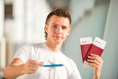 Young man with small airplane in airport waiting his flight Stock Photography