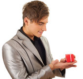 Young man with small red gift box on palm Stock Image