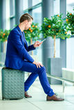 Young man with smart phone in airport. Caucasian man with cellphone at the airport while waiting for boarding. Urban businessman talking on smart phone inside in royalty free stock photo