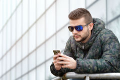 Young man with a smart phone. Young man posing with a smart phone in his hands Royalty Free Stock Images