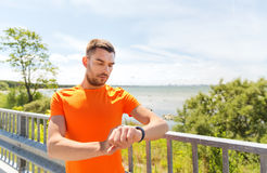 Young man with smart wristwatch at seaside Stock Images