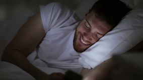 Young man with smartphone in bed at night stock video