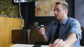 Young man with smartphone at cafe stock video footage
