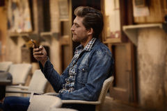 Young man with smartphone in an cafe outdoor Stock Photography