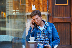 Young man with smartphone in an cafe outdoor Royalty Free Stock Photos