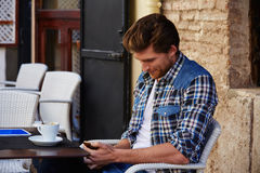 Young man with smartphone in an cafe outdoor Royalty Free Stock Images