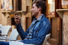 Young man with smartphone in an cafe outdoor Stock Images