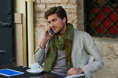 Young man with smartphone in an cafe outdoor Stock Image