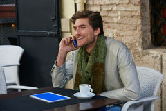 Young man with smartphone in an cafe outdoor Royalty Free Stock Photography
