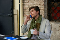 Young man with smartphone in an cafe outdoor Royalty Free Stock Image