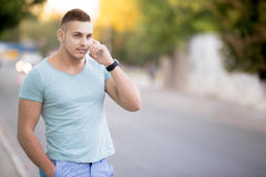 Young man on smartphone on city street Royalty Free Stock Photos