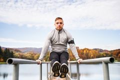 Young man with smartphone doing exercise in park. Stock Image