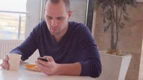 Young man with smartphone eating sandwich in cafe stock video