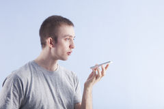 Young man with smartphone in hand makes a voice request. Young man with smartphone makes a voice request or audio recording. Blue wall background Stock Images