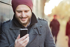 Young man with smartphone. Young man looking on smartphone in the city Royalty Free Stock Photography