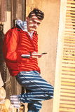 Young man with smartphone outdoor covered with sunlight shadow Royalty Free Stock Photography