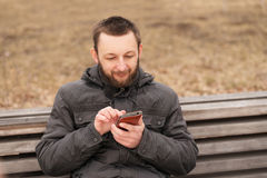 Young man with a smartphone outdoors Stock Photography