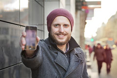 Young man with smartphone. Young man showing his smartphone in the city Stock Images