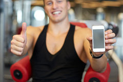 Young man with smartphone showing thumbs up in gym Stock Photos