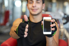 Young man with smartphone showing thumbs up in gym Stock Photography