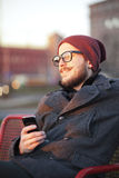 Young man with smartphone. Young smiling man with smartphone on the city bench Stock Images