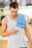 Young man with smartphone and towel in gym. Fitness, sport, training, gym, technology and lifestyle concept - young man with smartphone and towel in gym stock photography