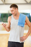 Young man with smartphone and towel in gym Stock Photos