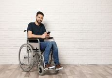 Young man with smartphone in wheelchair near brick wall indoors. Space for text royalty free stock photos