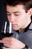 Young Man smelling a glass of red wine Royalty Free Stock Image