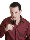 Young man smelling red wine. Young dark-haired man with red shirt and glass of red wine isolated on white background Stock Photography