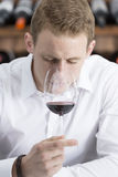 Young man smelling a red wineglass. Young man on a wine tasting session on the olfactory phase is analyzing the wine with the wineglass in the nose Stock Photography