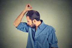Young man, smelling, sniffing his armpit, something stinks Royalty Free Stock Photos