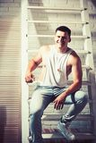 Young man smile on ladder. Guy in trendy tank top and jeans fashion. Athletic macho with muscular chest and hands stock image