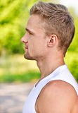 Young man smiles. Profile face of young man smiles against summer park Royalty Free Stock Photo